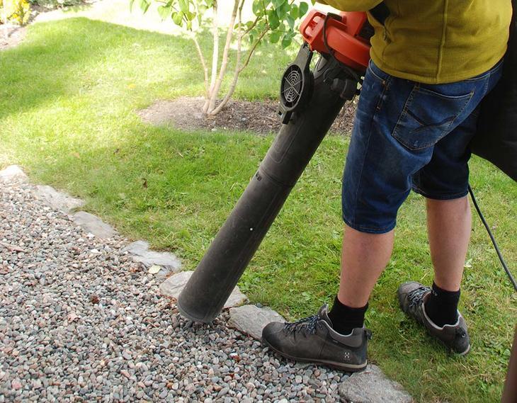 En mann fjerner løv fra grus med en løvblåser.