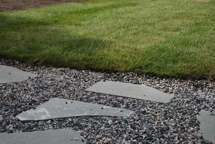En overgang av grus mot plen. I grusen ligger tråkkheller av skifer nedfelt.