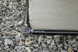 Hovedrør til dryppvanningsanlegg ligger tett innved en grunnmur. responsive-focuspoint focus-horizontal-50 focus-vertical-50