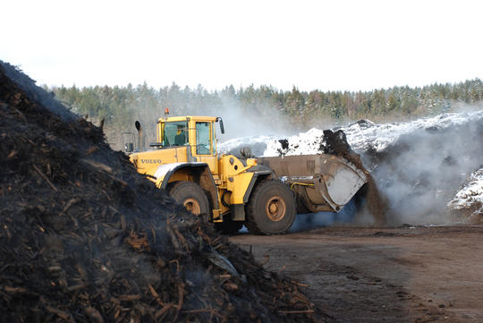 Hjullaster graver i en stor haug med kompostjord som damper selv om det er snø og vinter.