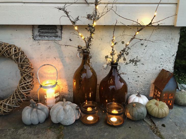 Støpte gresskar i betong sammen med ekte gresskar, lys og kviser i vase står i hagen til pynt.