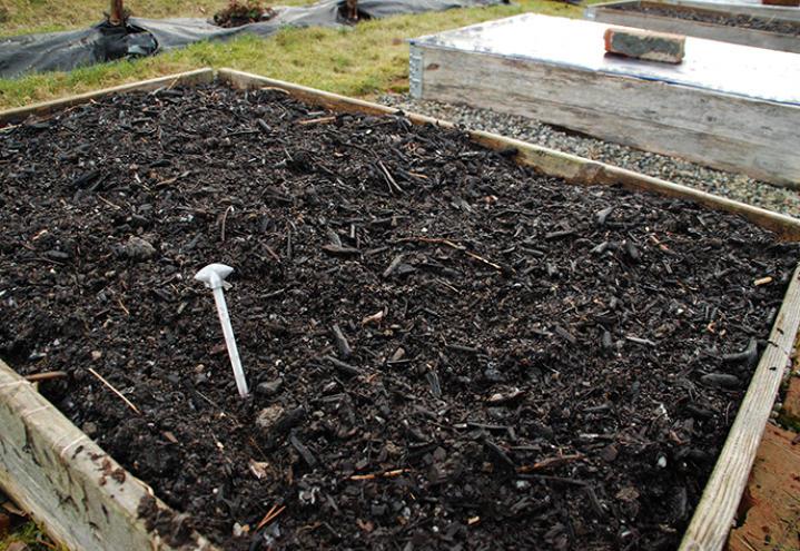 Et termometer stukket i jorda i en pallekarm tidlig om våren.
