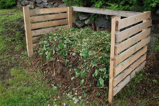 Hjemmesnekret hagekompostbinge med kompost dekket av rogneblader