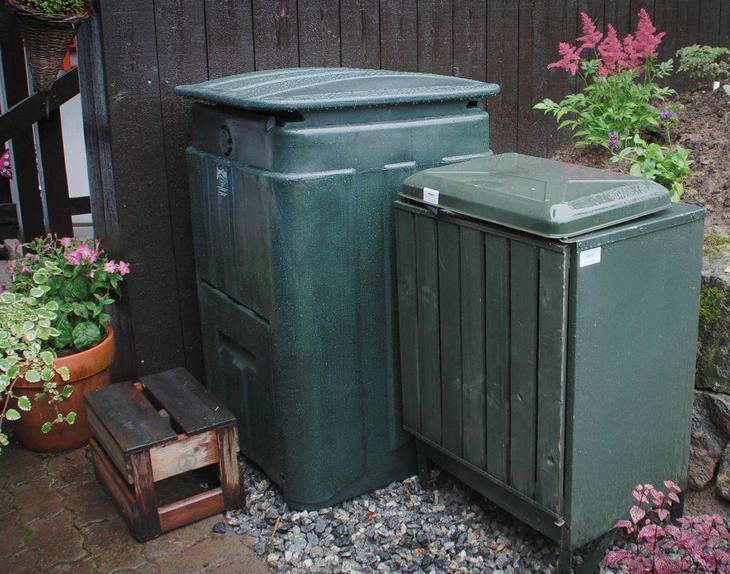 En varmkompostbinge side om side med en søppeldunk.