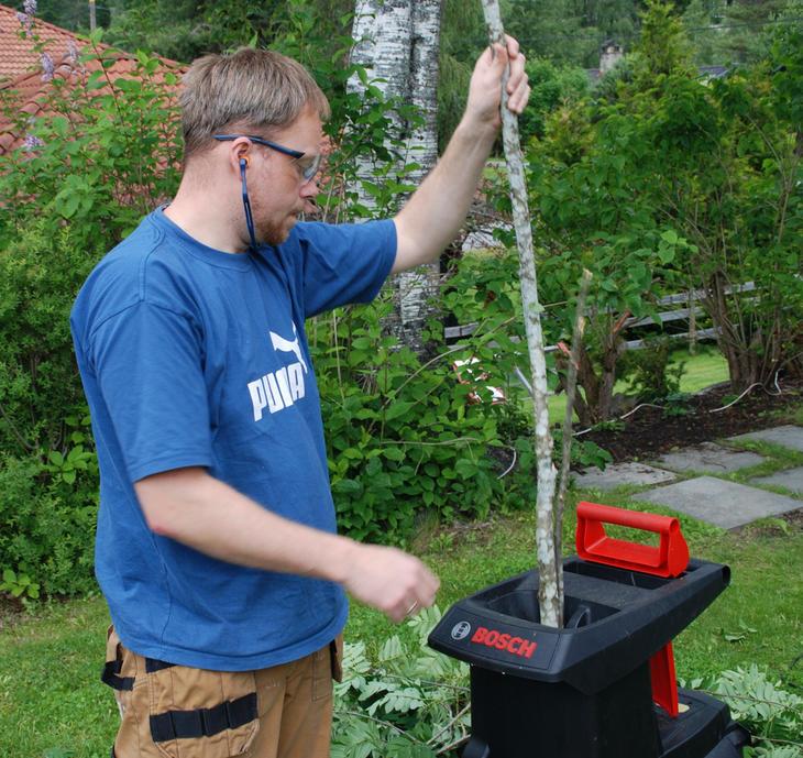 En mann kverner kvist fra hagen i en kompostkvern.